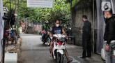 Pengendara sepeda motor disemprot cairan disinfektan saat akan memasuki pemukiman warga di kawasan H. Gari, Pesanggrahan, Jakarta, Jumat (3/4/2020). Penyemprotan secara swadaya tersebut dilakukan warga untuk mencegah penyebaran virus corona COVID-19. (Liputan6.com/Johan Tallo)