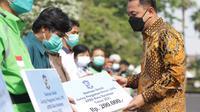 Eri Cahyadi menyerahkan bansos JPS masing-masing senilai Rp 200 ribu kepada 15 MBR di halaman Balai Kota Surabaya. (Dian Kurniawan/Liputan6.com)