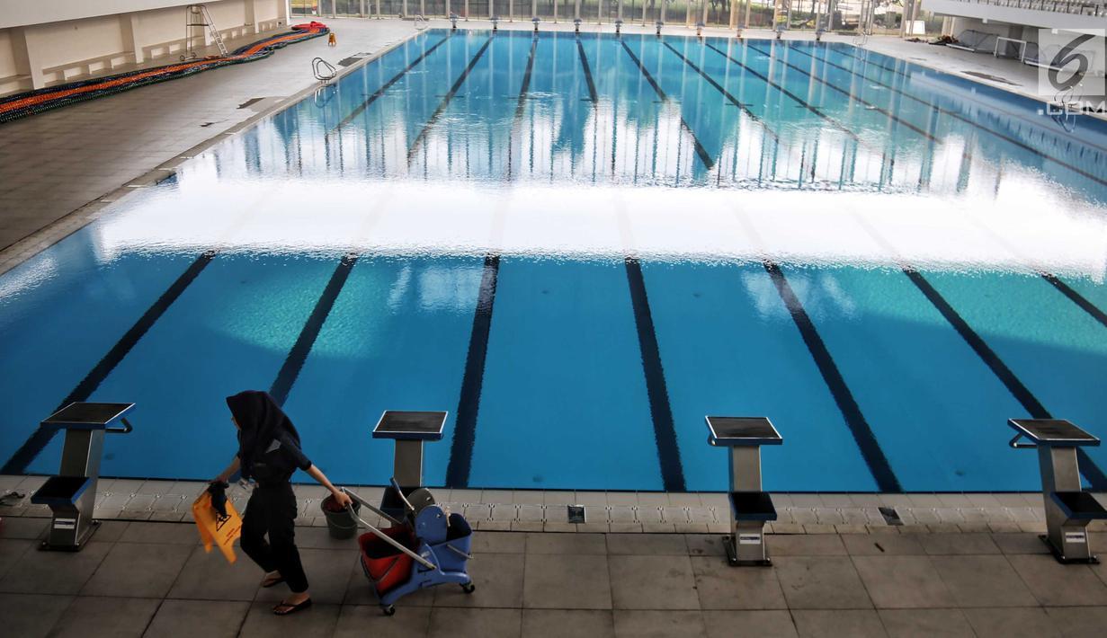 Petugas kebersihan berjalan dekat kolam Stadion Akuatik Gelora Bung Karno (GBK), Jakarta, Rabu (11/7). Stadion ini memiliki 3 kolam utama dan 1 kolam pemanasan berstandar Olimpiade dari FINA (Federasi Renang Internasional). (Liputan6.com/Faizal Fanani)
