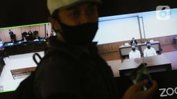 Pengunjung melintasi layar monitor yang menampilkan dua terdakwa penyiraman air keras terhadap penyidik KPK Novel Baswedan, Rahmat Kadir Mahulette (kanan) dan Rony Bugis yang mengikuti sidang putusan secara teleconference di PN Jakarta Utara, Kamis (16/7/2020). (Liputan6.com/Helmi Fithriansyah)