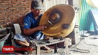 Suwanto memperbaiki gong di bengkelnya, Jalan Pande, Desa Junrejo, Kecamatan Junrejo, Kota Batu. (TIMES Indonesia/Ferry)