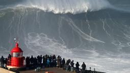 Warga menyaksikan aksi peselancar asal Jerman, Sebastian Steudtner saat menaklukan ombak selama sesi surfing ombak besar di Praia do Norte di Nazare, Portugal tengah (13/1). (AP Photo / Armando Franca)