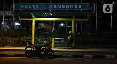 Pengemudi ojek daring beristirahat di halte Kemenkes, Jalan HR Rasuna Said, Jakarta, Kamis (2/4/2020). Pemerintah menetapkan Pembatasan Sosial Berskala Besar dengan membatasi kegiatan tertentu penduduk di wilayah yang diduga terinfeksi COVID-19. (Liputan6.com/Helmi Fithriansyah)