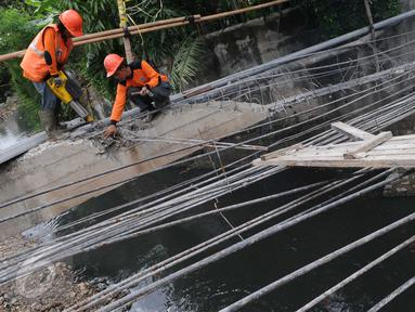 Petugas Suku Dinas Bina Marga Jakarta Barat memperbaiki Jembatan Kali Inspeksi Grogol, Jakarta, (30/5/2016). Amblesnya jembatan yang terletak depan kompleks Hankam, Palmerah tersebut penyebabnya diduga terjadi pergeseran tanah (Liputan6.com/Helmi Afandi)