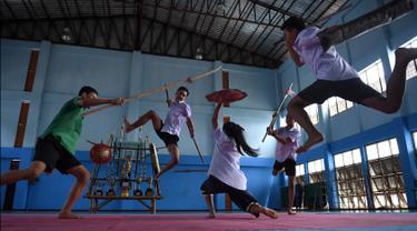 Seorang gadis menangkis serangan empat anak laki-laki yang menggunakan pedang selama berlatih Krabi Krabong di sekolah Thonburee Woratapeepalarak, Thonburi, Bangkok (8/7/2019). Krabi Krabong merupakan seni bela diri Thailand yang dipersenjatai pisau dan perisai kayu. (AFP Photo/Lillian Suwanrumpha)