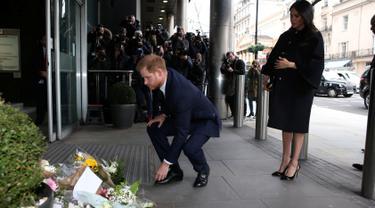 Pangeran Harry dan Meghan Markle meletakkan karangan bunga sebagai penghormatan kepada para korban serangan teror di Christchurch saat mengunjungi Komisi Tinggi Selandia Baru di London, Selasa (19/3). (Ian Vogler/Pool via REUTERS)