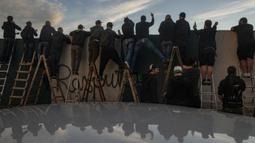 Suporter Bohemians 1905 menyaksikan pertandingan Czech First League alias Liga Fortuna melawan Sparta Praha dari balik tembok di Praha, Rep. Ceko pada 6 Juni 2020. Dengan menggunakan tangga, mereka menonton laga yang tertutup di tengah pembatasan virus corona Covid-19. (Michal Cizek/AFP)