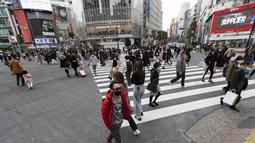 Orang-orang, yang mengenakan masker wajah, berjalan melintasi persimpangan di Tokyo (11/12/2020). Tokyo melaporkan 621 kasus COVID-19 baru pada hari Sabtu, 12 Desember, menetapkan level tertinggi baru di ibu kota Jepang. (AP Photo / Hiro Komae)