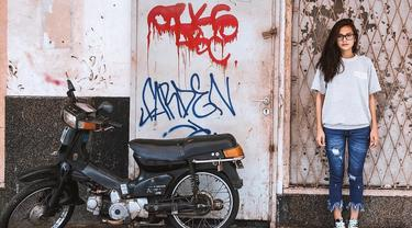 Indah sering tampil santai menggunakan sneakers. Berpose di samping sebuah motor tua, ia tampil menggunakan baju abu-abu dengan celana denim. walaupun tampak tomboy, rambutnya yang terurai ke samping membuat kecantikannya tidak pernah pudar. (Liputan6.com/IG/@indahpermatas)