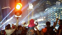 Warga menyaksikan hiburan menggunakan telepon genggam pada malam puncak peringatan HUT DKI Jakarta ke-492 di Bundaran HI Jakarta, Sabtu, (22/6/2019). Peringatan HUT Jakarta yang dibuka Gubernur DKI Jakarta Anies Baswedan dikemas dalam konsep ekonomi kreatif dan seni. (Liputan6.com/Immanuel Antonius)