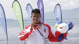 Atlet modern pentathlon, Muhammad Taufik, menunjukan medali usai meraih perunggu pada nomor beach triathle individual SEA Games 2019 di Subic, Jumat (6/12). Dirinya membukukan catatan waktu 00:17:37.76.  (Bola.com/M Iqbal Ichsan)