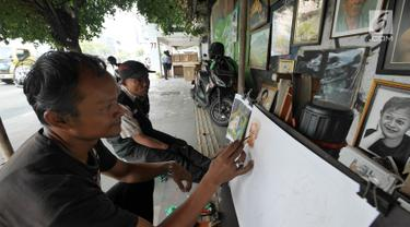 Seorang pelukis melukis di trotoar Kawasan Glodok, Jakarta, Selasa (15/5). Pelukis trotoar yang terhimpun dalam kelompok pelukis Kota ini menjual hasil lukisannya dan juga menawarkan jasa lukis potret. (Liputan6.com/Herman Zakharia)