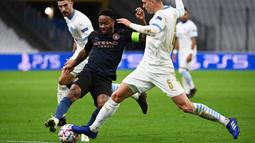 Penyerang Manchester City, Raheem Sterling, berebut bola dengan bek Olympique Marseille, Leonardo Balerdi, pada laga Liga Champions 2020/2021 di Stadion velodrome, Rabu (28/10/2020) dini hari WIB. Manchester City menang 3-0 atas Marseille. (AFP/Christophe Simon)