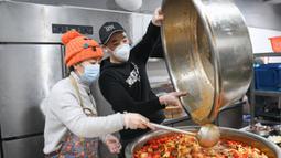 Liu (kiri) bersama rekan timnya menyiapkan makanan untuk para petugas medis di Wuhan, Provinsi Hubei, China, Rabu (26/2/2020). Di Wuhan, Liu bersama beberapa koki memasak dan mengantar makanan secara gratis untuk para petugas medis yang berjuang melawan virus corona COVID-19. (Xinhua/Cheng Min)