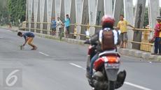 Seorang bocah mengambil uang yang dilempar pengguna jalan di Jembatan Cikalong, Jawa Barat, Sabtu (2/7). Memasuki mudik Lebaran, jumlah pencari uang sedekah di kawasan itu meningkat dibanding hari biasa (Liputan6.com/Gempur M Surya)