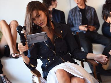 Model cantik Bella Hadid berselfie saat berada di belakang panggung Michael Kors Spring 2017 sebelum Tampil di New York Fashion Week, AS, (14/9).  Model 19 tahun ini terlihat gembira memainkan kameranya. (AFP Photo/Dimitrios Kambouris)