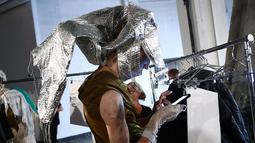 Seorang model memainkan gadgetnya di belakang panggung saat bersiap membawakan busana VFILES selama New York Fashion Week di Barclays Center of Brooklyn di New York City, (6/9). (Astrid Stawiarz / Getty Images / AFP)
