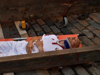 Seorang peserta ditandu tim medis setelah diseruduk banteng dalam Festival San Fermin di Pamplona, Spanyol utara, (9/7). Ratusan orang dari seluruh dunia  setiap tahunnya ambil bagian dalam Festival Adu Banteng, San Fermin. (AP Photo/Alvaro Barrientos)
