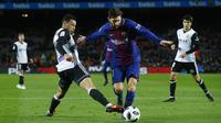 Striker Barcelona, Lionel Messi, berusaha melewati gelandang Valencia, Francis Coquelin, pada laga leg pertama semifinal Copa Del Rey di Stadion Camp Nou, Jumat (2/2/2018). Barcelona menang 1-0 atas Valencia. (AP/Manu Fernandez)