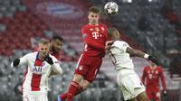 Pemain Bayern Munchen, Joshua Kimmich, duel udara dengan pemain Paris Saint-Germain (PSG), Presnel Kimpembe, pada laga Liga Champions di Allianz Arena, Kamis (8/4/2021). PSG menang dengan skor 3-2. (AP Photo/Matthias Schrader)
