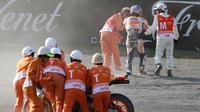Pebalap Repsol Honda, Dani Pedrosa, mendapat bantuan dari marshal dan staf medis untuk berjalan keluar trek setelah mengalami kecelakaan hebat pada sesi latihan bebas kedua MotoGP Jepang di Twin Ring Motegi, Jumat (14/10/2016). (Crash)