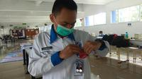 M. Rafhi Rihadatusyawal dari SMK Mitra Industri MM2100, Jawa Barat menguji alat penjaga jarak fisik temuannya. Rafhi merupakan pemenang pada level Gold pada ajang AHM Best Student 2020.