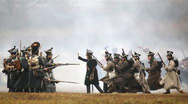 Sejumlah peserta berpakaian seperti tentara Rusia dan Prancis tahun 1812 melakukan adegan pertempuran di Belarus (26/11). Mereka melakukan reka ulang pertempuran Berezina yang terjadi pada tahun 1812.  (AP Photo/Sergei Grits)