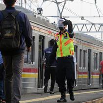 Petugas stasiun memandu penumpang KRL Commuterline di Stasiun Bogor, Jawa Barat, Selasa (9/6/2020) pagi. Puluhan polisi, TNI, Satpol PP, dan petugas stasiun diterjunkan untuk memandu penumpang mengantisipasi antrean panjang seperti kemarin. (merdeka.com/Arie Basuki)