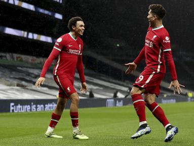Bek Liverpool, Trent Alexander-Arnold (kiri) berselebrasi dengan rekannya Roberto Firmino usai mencetak gol ke gawang Tottenham Hotspur pada pertandingan lanjutan Liga Inggris di Stadion Tottenham Hotspur, London, Jumat (29/1/2021). Liverpool menang atas Tottenham 3-1. (Catherine Ivill/Pool via AP)
