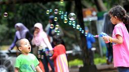 Anak-anak bermain gelembung saat berkunjung ke Ragunan, Jakarta, Minggu (25/12). Ragunan masih menjadi tempat favorit warga untuk mengisi libur panjang. (Liputan6.com/Helmi Afandi)