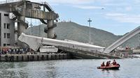 Tim penyelamat menggunakan kapal kecil bersiap mengevakuasi dalam pekerjaan kapal di lokasi jembatan yang ambruk di pelabuhan Nanfangao di kota Suao (1/10/2019). Dilaporkan beberapa nelayan diduga masih terjebak di perahu yang tertimpa material perahu ke dasar laut. (AFP Photo/Sam Yeh)