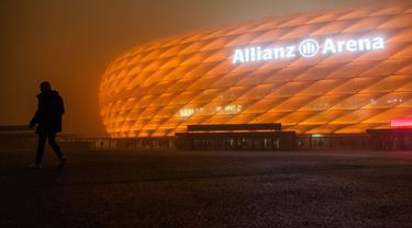"""Allianz Arena, markas dari FC Bayern Munchen, diterangi warna oranye untuk kampanye """"Orange the World"""" di Munich, Jerman, Senin (25/11/2019). Cahaya berwarna oranye untuk melambangkan partisipasi mendukung penghapusan kekerasan terhadap perempuan. (Lino Mirgeler/dpa/AFP)"""