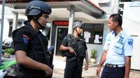 Personel polisi berjaga di sekitar Dermaga Wijayapura menuju LP Nusakambangan, Cilacap, Jateng,dengan menyandang senjata laras panjang, Kamis (28/7). Jelang eksekusi mati, kepolisian melakukan sterilisasi di Pulau Nusakambangan (Liputan6.com/Helmi Afandi)