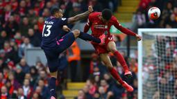 Bek Liverpool, Joe Gomez, berebut bola dengan pemain Bournemouth pada laga lanjutan Premier League 2019-2020 di Anfield, Liverpool, Sabtu (7/3) malam WIB. Liverpool menang 2-1 atas Bournemouth. (AFP/Geoff Caddick)