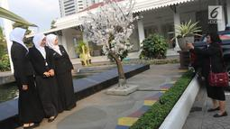 Sejumlah pegawai foto di samping pohon imitasi yang terpasang di halaman Balai Kota DKI Jakarta, Senin (4/6). Sebelumnya, pohon imitasi itu dipasang di trotoar yang ada di Jalan Medan Merdeka Barat, Thamrin hingga Sudirman. (Liputan6.com/Arya Manggala)