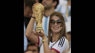 Seorang wanita suporter Jerman tampak memegang trofi Piala Dunia, Brasil, Senin (14/7/14). (AFP/JUAN MABROMATA)