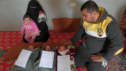 Pasangan Nidal dan Islam Al-Saiqli berpose dengan bayi kembar mereka, Jerusalem, Capital dan Palestine di Khan Yunis, Jalur Gaza, Jumat (2/2). Pasangan Nidal dan Islam memberi nama unik kepada tiga bayi kembar mereka yang baru lahir. (SAID KHATIB/AFP)