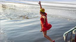 Seorang wanita melompat untuk berenang di danau  yang sebagaian beku dengan es saat suhu minus 20 derajat Celcius di Shenyang di provinsi Liaoning timur laut China (10/12). (AFP Photo/Str/China Out)