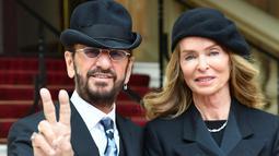 Ringo Starr berpose dengan istrinya Barbara Bach saat tiba untuk menerima gelar kebangsawanan dari kerajaan Inggris di Istana Buckingham, di London (20/3). Ringgo diberi gelar 'Sir' atas jasanya dalam dunia musik. (John Stillwell / Pool Photo via AP)