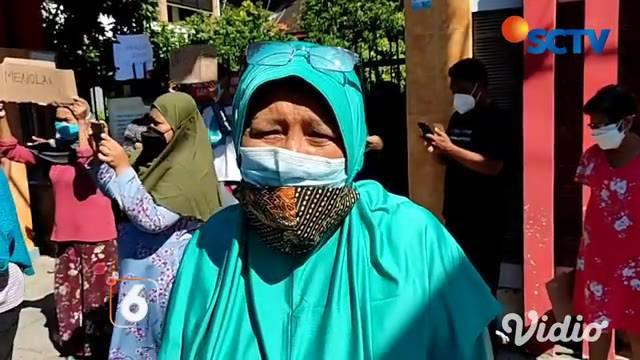 Puluhan warga demo tolak sekolah dijadikan tempat isolasi, di depan SD Negeri Barata Jaya, Surabaya pada Jumat (23/7) siang. Warga mengaku khawatir terpapar Covid-19, jika sekolah dijadikan tempat isolasi.
