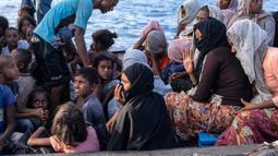Pengungsi etnis Rohingya berada di atas kapal milik nelayan Indonesia di pesisir Pantai Seunuddon, Aceh Utara (24/6/2020).  Para pengungsi Rohingya diselamatkan nelayan Aceh setelah kapal yang ditumpangi puluhan pengungsi itu rusak. (AP Photo/Zik Maulana)
