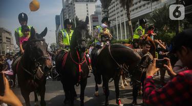 Sejumlah anak berfoto dengan polisi berkuda dari Direktorat Polisi Satwa Mabes Polri di kawasan Bundaran HI, Jakarta, Minggu (17/11/2019). Polisi berkuda tersebut khusus ditugaskan mengawasi keamanan CFD serta memperkenalkan kepada warga. (Liputan6.com/Faizal Fanani)