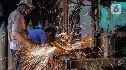 Pekerja melakukan pengelasan saat membongkar Koperasi Angkutan Jakarta (Kopaja) yang akan diremajakan di kawasan Meruya, Jakarta Barat, Rabu (27/1/2021). Kopaja yang tak lagi digunakan tersebut dihancurkan untuk dijual secara kiloan ke penjual besi tua. (Liputan6.com/Johan Tallo)
