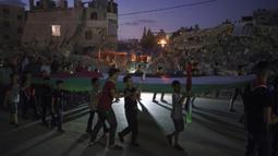 Anak-anak memegang bendera Palestina dalam demonstrasi mendukung keluarga yang kehilangan rumahnya di Beit Lahia, Jalur Gaza, Jumat (4/6/2021). Kendati gencatan senjata telah dilakukan, salah satu masalah yang lebih dalam terkait konflik Israel-Palestina tidak pernah dibahas. (AP Photo/Felipe Dana)