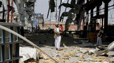 Seorang pria menggendong anaknya di sebuah bangunan pabrik pipa dan pompa air yang hancur akibat serangan udara Arab Saudi di Sanaa, Yaman, Kamis (15/9). Dalam serangan ini tidak ada korban jiwa. (REUTERS/Khaled Abdullah)