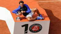 Petenis Rafael Nadal berpose dengan trofinya usai mengalahkan Stan Wawrinka pada final Prancis Terbuka di Roland Garros, Minggu (11/6). Atas kemenangan ini, Nadal sukses meraih gelar La Decima alias ke-10 di Prancis Open 2017. (AP Photo/Petr David Josek)