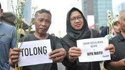 Warga berpose dengan bunga yang diberikan dalam Aksi Selamatkan KPK di hari bebas kendaraan bermotor kawasan Bundaran HI, Jakarta, Minggu (8/9/2019). (merdeka.com/Iqbal S. Nugroho)