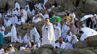 Jemaah haji mengunjungi bukit Jabal Rahmah di Padang Arafah, sebelah tenggara kota suci Makkah, Arab Saudi, Sabtu (10/8/2019). Menjelang Wukuf Arafah, Jabal Rahma yang terletak di Padang Arafah banyak dikunjungi peziarah haji. (FETHI BELAID / AFP)