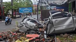 Pengendara motor melewati rongsokan mobil yang rusak akibat gempa bumi di Mamuju, Sulawesi Barat, Sabtu (16/1/2021). Petugas Badan Penanggulangan Bencana Daerah (BPBD) masih mendata jumlah kerusakan dan korban akibat gempa bumi tersebut. (AP Photo/Yusuf Wahil)