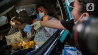 Relawan membagikan masker kepada pengemudi mobil di Bundaran HI, Jakarta, Selasa (17/3/2020). Sebanyak 3.000 masker dibagikan gratis kepada pengguna jalan sebagai bentuk keprihatinan sekaligus berpartisipasi dalam upaya mencegah penyebaran virus corona COVID-19. (Liputan6.com/Faizal Fanani)